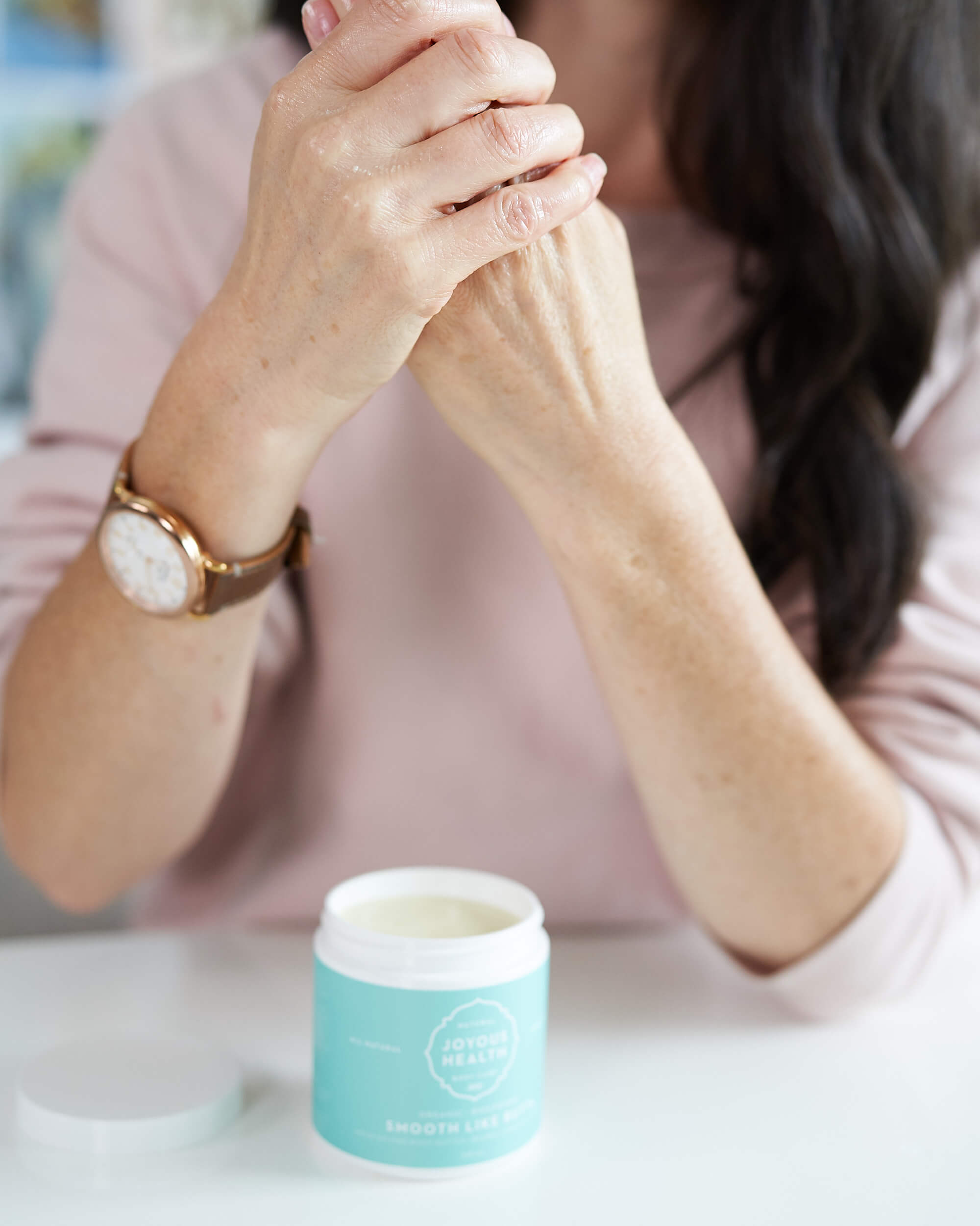 Woman with dark hair putting on hand cream.