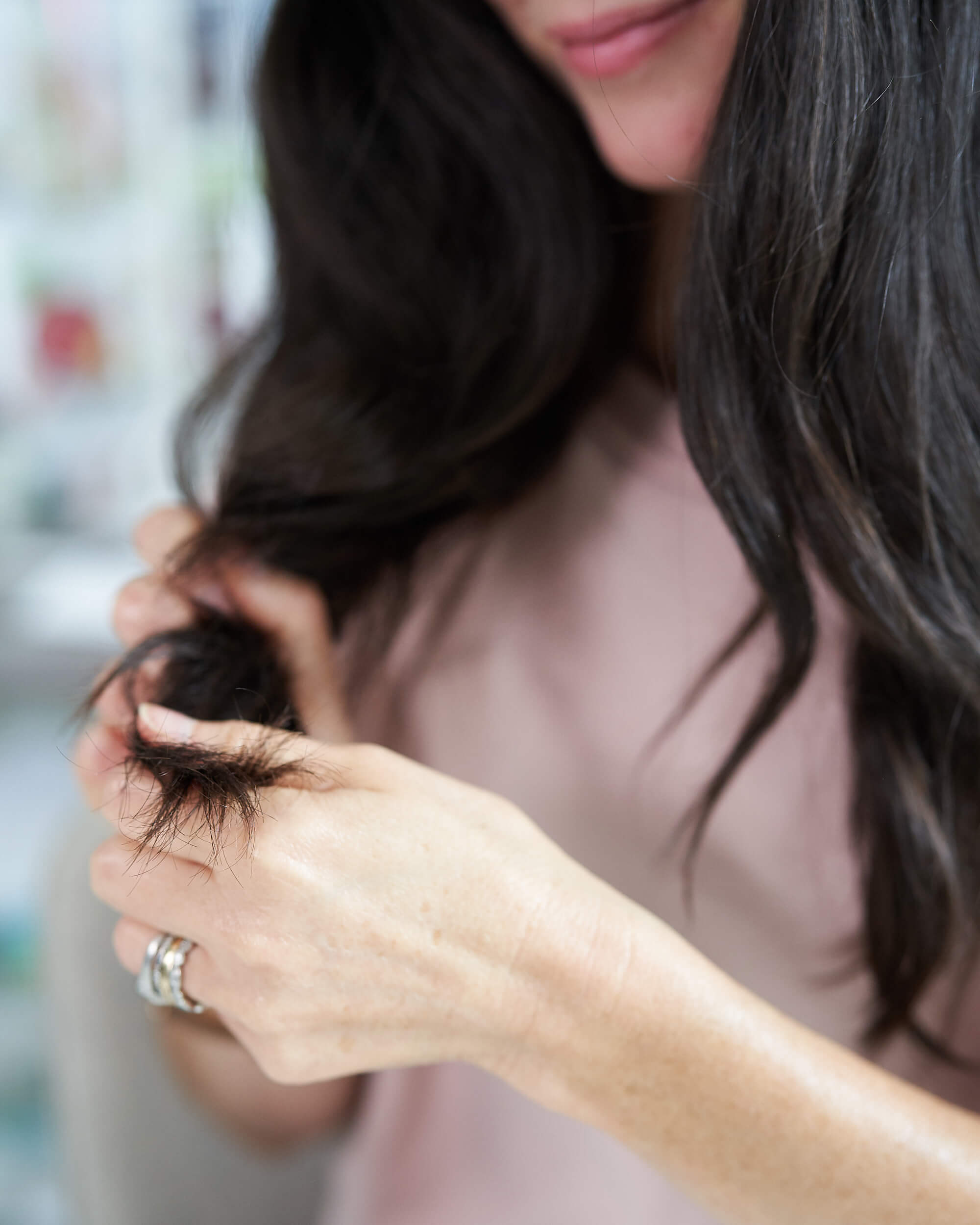 Woman with dark hair putting serum in hair.